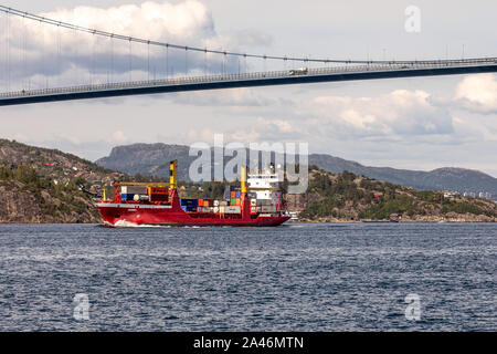 Small container vessel Rumba passing under Askoy (Askøy) suspension bridge, outside port of Bergen, Norway - Stock Photo