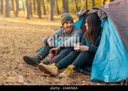 Romantic couple camping outdoors, sitting in tent - Stock Photo