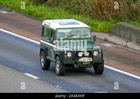 1973 green Land Rover 90 Defender Turbo Diesel; UK Vehicular traffic, transport, modern, saloon cars, south-bound on the 3 lane M6 motorway highway. - Stock Photo