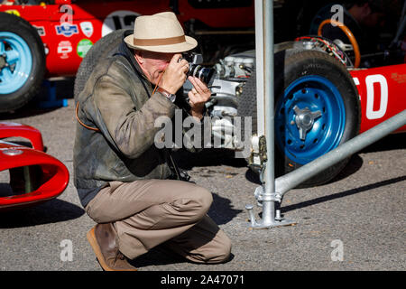 Man photographing cars in the paddock area at the 2019 Goodwood Revival, Sussex, UK. Historic and classic motorsport event. - Stock Photo