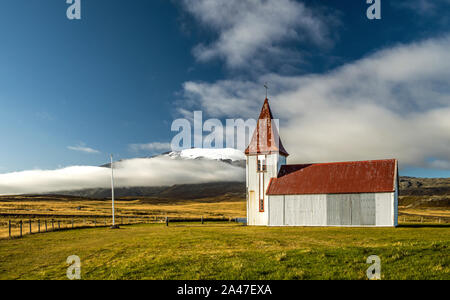 Disused Icelandic Church at Hellnar with white walls and a red roof and spire on the Snaefellsnes Iceland - Stock Photo