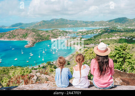 Family enjoying the view of picturesque English Harbour at Antigua. View of paradise bay at tropical island in the Caribbean Sea. Family vacation. - Stock Photo