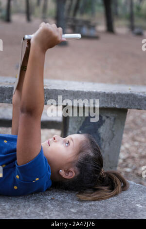 Girl eight years old is lying down on a picnic table watching a video on her touchpad. Vertical photo - Stock Photo