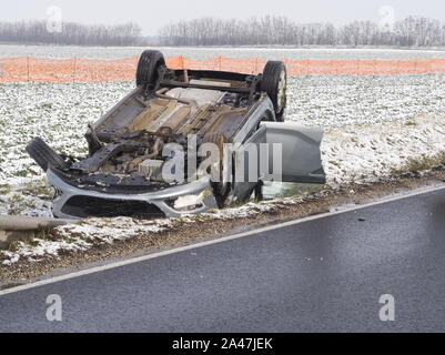 Overturned Car Beside the Wet Road on a Winter Day - Stock Photo