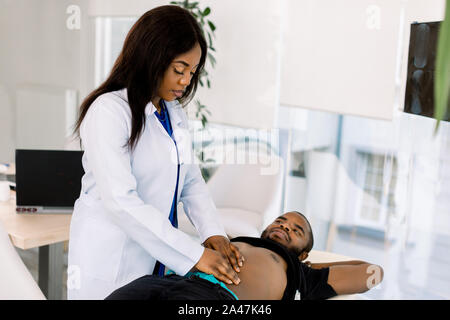 Sick and stomachache African man being examined by the female doctor. Doctor pressing his patient's stomach, checking the area of pain - Stock Photo