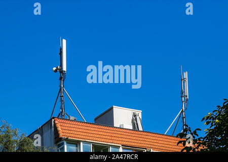 Two antennas of cellular communication on an orange tiled roof of a multi-storey residential building against blue sky. Low angle view. - Stock Photo