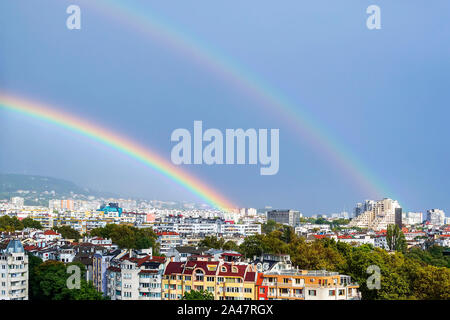 Gorgeous double rainbow over city. A double rainbow appeared against gray stormy sky over residential area of the city. Beauty in nature. - Stock Photo
