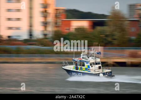 Met Police boat providing security for a warship visiting the River Thames in East London - Stock Photo