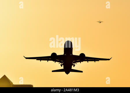 Plane taking off from London City airport with golden skies as the sun sets behind the Canary Wharf skyline - Stock Photo