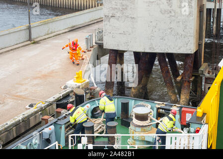 Port staff cast off the mooring ropes on a car ferry as it leaves the harbour at Uig on the Isle of Skye bound for Tarbert on Harris, Outer Hebrides. - Stock Photo