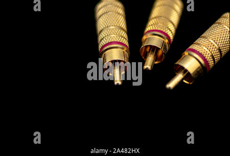 three golden and metallic rca connectors in the foreground on black background - Stock Photo