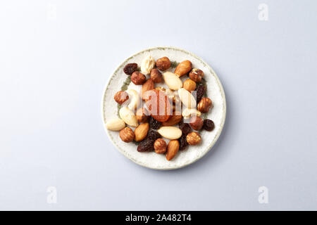 Nuts, raisins and apricots on bright paper background. Concept for healthy snack. Copy space. - Stock Photo