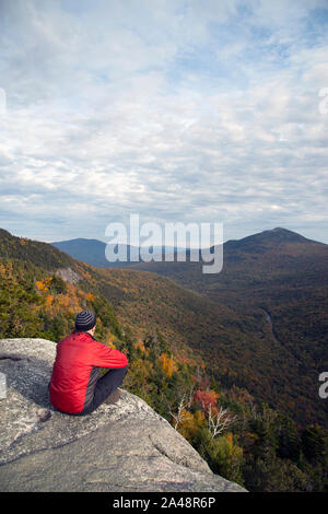 Hiker on Table Rock trail summit, looking down over cliff edge, Grafton Notch State Park, Maine, October - Stock Photo