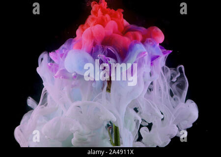 Splashes of colored ink in water, bright colors. Creative and color mix, abstract swirls of different colors on a black background