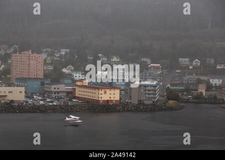 Ketchikan, Alaska, United States - September 26, 2019: Beautiful Aerial View of an Airplane Landing on water in front of a small touristic town in the