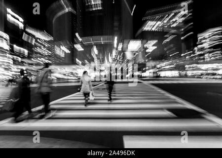 Pedestrians crossing the street at the heart of Ginza District in Tokyo. Ginza crossing at night. Blurred motion. - Stock Photo
