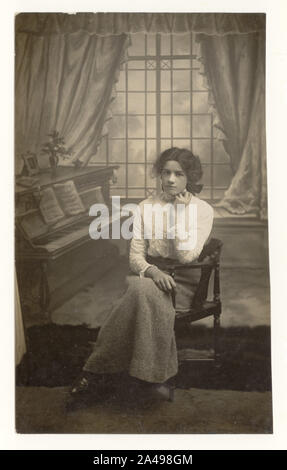 Edwardian studio portrait, cut down postcard of pretty young woman or late teens girl seated by piano prop, wearing high necked lace blouse and woollen skirt, circa 1910, 1911, U.K. - Stock Photo