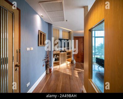 Luxury room decor with brown wooden floor and furniture in warm light and window glasss for see view outside, room of hotel resort in Thailand. - Stock Photo