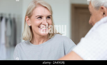 Focus on caregiver face female assisting patient listening older man - Stock Photo