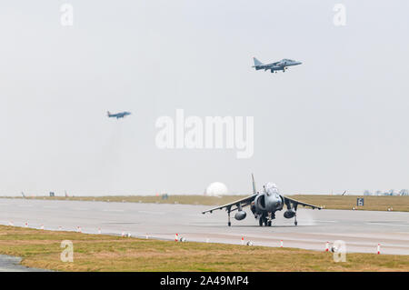 RAF Harrier GR9 taxiing on runway with Harriers landing behind after final flight on 15th December 2010, RAF Cottesmore - Stock Photo