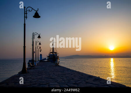 Pier and wooden motor boat at sunrise, used for tourist trips on the sea, Pefkohori, Greece. - Stock Photo