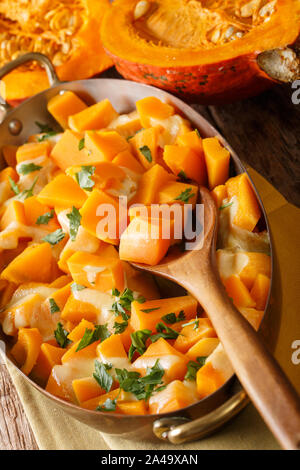 Tasty traditional pumpkin casserole with mozzarella cheese close-up in a baking dish on the table. vertical - Stock Photo