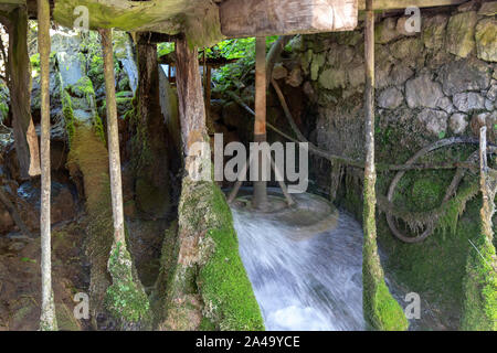Water wheel at the old grist mill. Water from a river flows under this mill, wooden paddles are placed in the flow to cause a rotation of the stone. B - Stock Photo