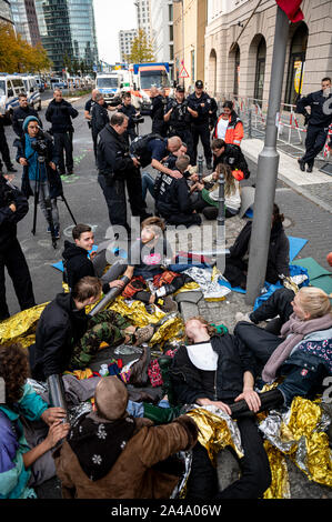 Berlin, Germany. 13th Oct, 2019. An activist of the climate movement 'Extinction Rebellion' has chained together in front of the Federal Ministry for the Environment. Credit: Fabian Sommer/dpa/Alamy Live News - Stock Photo
