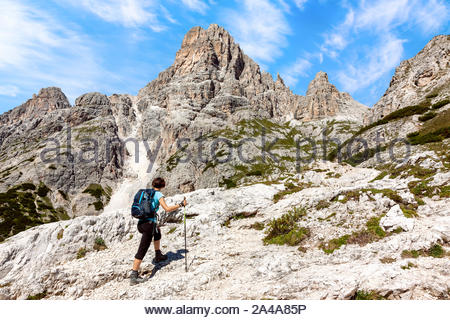 Woman hiking in scenic mountains, hiking trail in Italian Dolomites, with breathtaking Alps landscape in summer day - Stock Photo