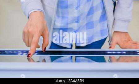 Woman using interactive touchscreen display kiosk - Stock Photo