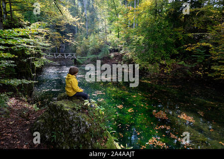 Young boy in yellow jacket sitting by a small lake near Snežnik castle, Slovenia - Stock Photo