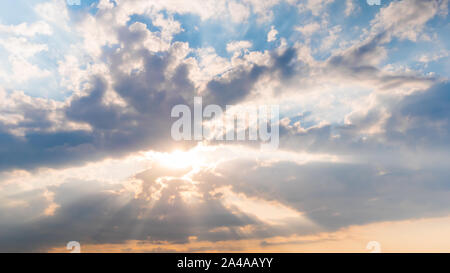 Sun beams shining through dramatic white clouds, hope and religion concept