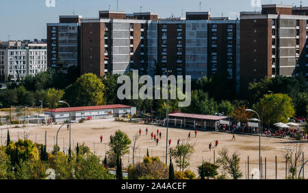 High perspective view of unidentifiable teenagers on a 11 a side amateur football match on a sandy patch in a residential neighbourhood. - Stock Photo