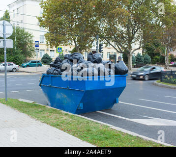 A full dumpster with garbage bags stands on the street road - Stock Photo