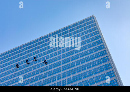 Four Window Washers on the Side of a Skyscraper - Stock Photo
