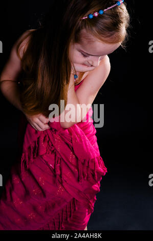 Beautiful little girl child.Little girl posing in studio with a cloth on a black background. A child with brown hair poses in a pink cape in the studi - Stock Photo