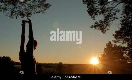 Young woman stretching towards the sky in forest at sunset - Stock Photo