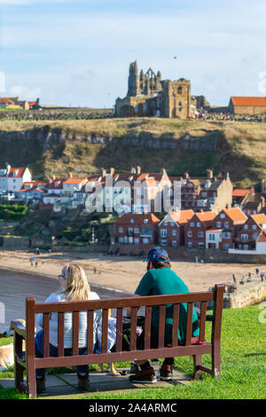 Man and woman sitting on a wooden bench overlooking the East Cliff beach below Whitby Abbey and The Church of Saint Mary - Stock Photo