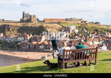 Man on West Cliff with Tablet taking photos of Whitby Abbey and The Church of Saint Mary on East Cliff - Stock Photo