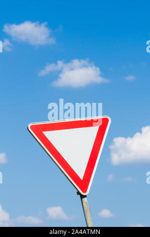 Single triangle road sign in red and white, give way, against blue sky and clouds - Stock Photo