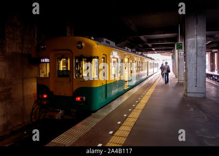 TATEYAMA, JAPAN - OCTOBER 5, 2018. The Train Has Arrived At In The Railway Station In Japan. Men Are Walking On The Platform Towards End Of Tunnel. - Stock Photo