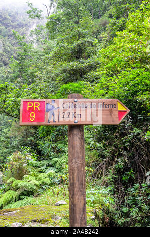 Tourist sign giving directions and distances on a hiking path in Caldeirao de Inferno, Madeira island, Portugal. Levada walking on Portuguese island. Green forest in the background. Information signs. - Stock Photo