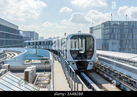 The Monorail Train Is Approaching Station On A Sunny Day. The White Metro Train Is Arriving To The Platform On Open Air Track In Tokyo, Japan. - Stock Photo
