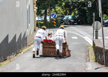 Monte, Madeira, Portugal - Sep 14, 2019: Toboggan ride with Carreiros do Monte. Traditional mean of transport, now a tourist attraction. People riding downhill with drivers. Wicker basket sled. - Stock Photo