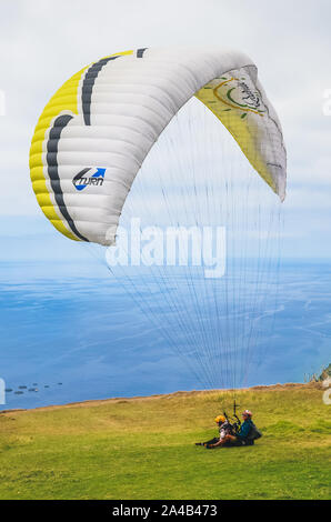 Arco da Calheta, Madeira, Portugal - Sep 16, 2019: Tandem paragliders landing on the cliffs above the Atlantic ocean. The blue seawater in the background. Paragliding, extreme sports. - Stock Photo
