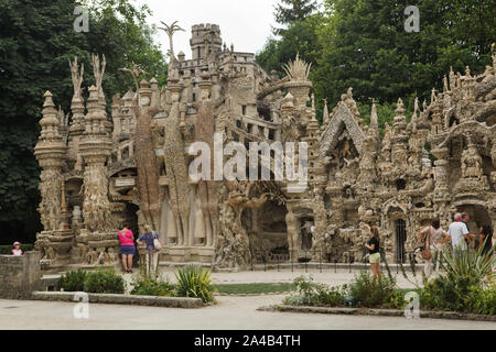 Visitors in front of the Ideal Palace (Le Palais idéal) designed by French postman Ferdinand Cheval and build from 1876 to 1912 in Hauterives, France. Roman dictator Julius Caesar, Celtic king Vercingetorix and Greek mathematician and physicist Archimedes are depicted from left to right as the Three Giants on the east facade. ATTENTION: This image is a part of a photo essay of 36 photos featuring the Ideal Palace (Le Palais idéal). - Stock Photo