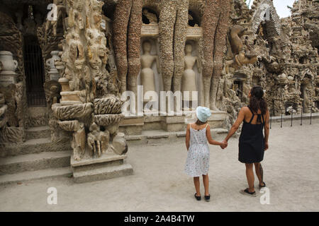Visitors in front of the Ideal Palace (Le Palais idéal) designed by French postman Ferdinand Cheval and build from 1876 to 1912 in Hauterives, France. Two Egyptian mummies are seen depicted on the east facade between legs of the Three Giants. ATTENTION: This image is a part of a photo essay of 36 photos featuring the Ideal Palace (Le Palais idéal). - Stock Photo