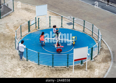 Children are Playing on The Playground While Their Mom is Watching. Kids are Riding Roundabout. Two Young Girls are Having Fun. - Stock Photo