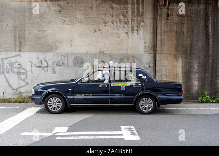 TOKYO, JAPAN - OCTOBER 8, 2018. Black Retro Japanese Taxi Cars. Taxi Driver is Waiting For Passengers. The Cap Driver is Having a Short Break. - Stock Photo