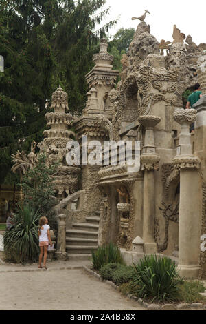 Young visitor in front of the west facade of the Ideal Palace (Le Palais idéal) designed by French postman Ferdinand Cheval and build from 1876 to 1912 in Hauterives, France. ATTENTION: This image is a part of a photo essay of 36 photos featuring the Ideal Palace (Le Palais idéal). - Stock Photo